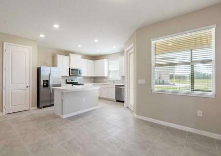 The living and kitchen area of the Calabria floor plan that has tile flooring a window and a door to the back patio.