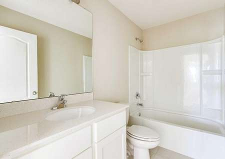 A bathroom in the St. Johns floor plan with a tub/shower combo and quarts countertops.