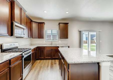 Roosevelt kitchen with granite counters, stainless steel appliances, and dark wood cabinets