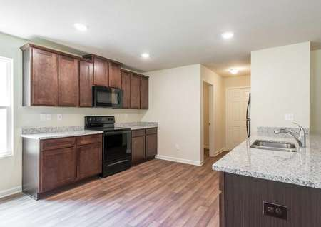 Lincoln finished kitchen with granite countertops, brown cabinets, and wood looking floor