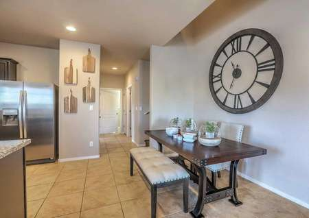 Sierra model home kitchen and dining area completed with stainless steel refrigerator, decorative cutting boards hanging on the wall, and a square wooden dining table with bowls on top and a cushioned bench