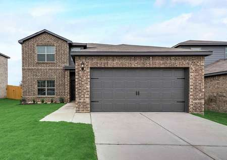 Oakmont brick exterior view with 2 car garage, shingle roof, and green grass landscaping