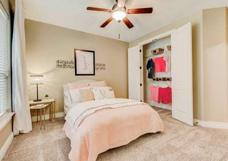 Mantle kid's bedroom with peach sheets on bed, brown ceiling fan, and open closet with clothes