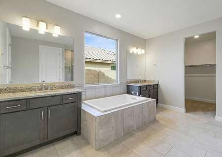 Hawley master bath with two granite vanities, brown cabinetry, and large framed-in bathtub