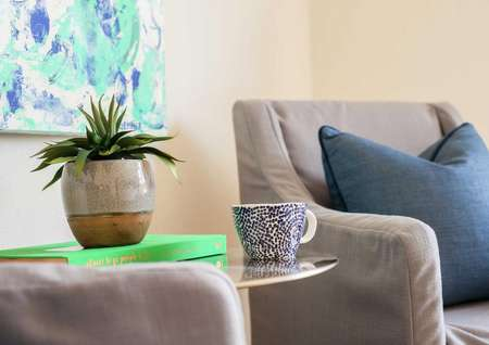 Staged home completed with two gray chairs one with blue pillow, small round table with vase with plant in it and blue cup beside, and turquoise colored painting hanging on the wall