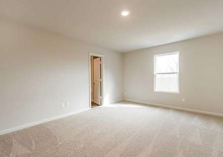 Camden bedroom with soft brown carpeting, light gray walls with white trim, and access to private bathroom