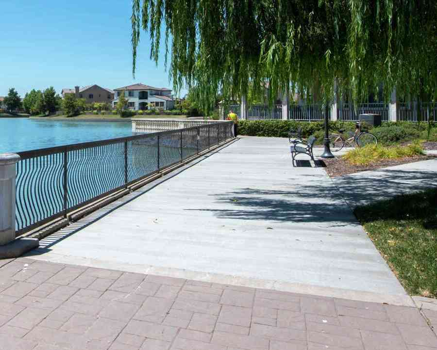 A walkway along a lake in the Bridgeway Lakes community a fence in between them.