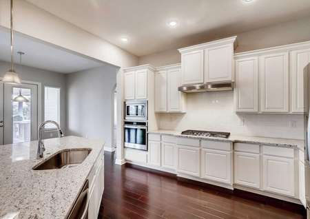 Timberline floor plan kitchen with white wooden cabinetry, dark wood floors, and recessed lighting