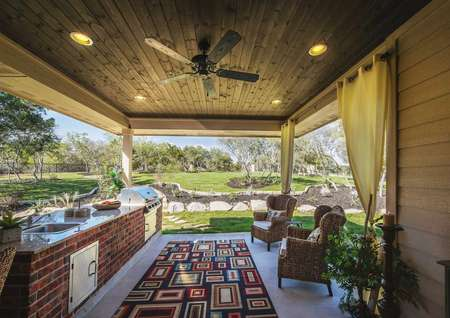 Covered outdoor kitchen with stainless grill, sitting area and ceiling fan.