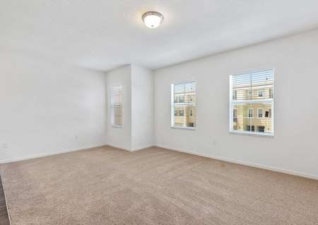 The light brown carpeted family room that has a ceiling light fixture and three windows.