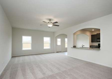Spacious living room with light-colored carpet, two windows, and a ceiling fan in the Rayburn floor plan