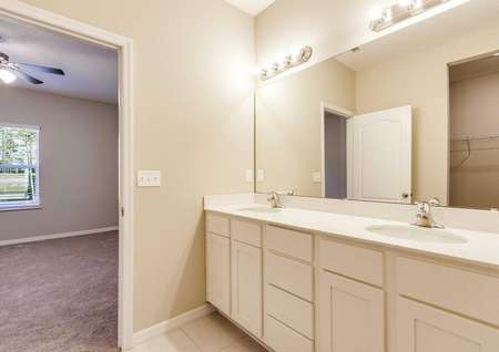 The master bedroom in the Wekiva floor plan with white cabinets, dual-vanity sinks and a view of the carpeted bedroom.