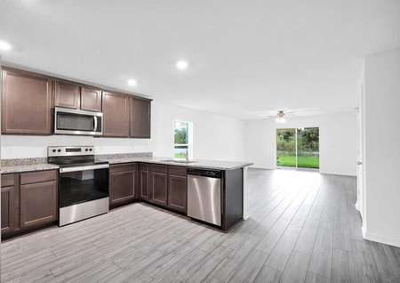 Kitchen angle with a view of stainless steel appliances and a large family room.