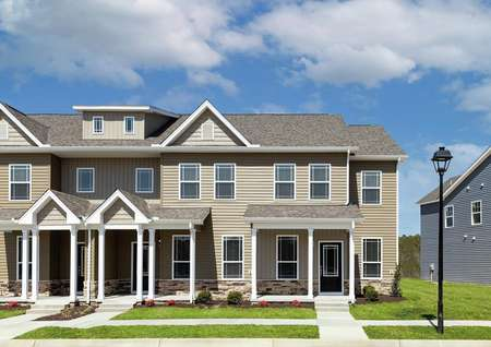 Angled view of the front elevation of a 4-unit townhome building at Huntington Pointe featuring from left to right the Hampton, Carol, William and York floor plans, tan paint, white trim, water table rocks.