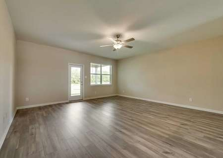 The open living room in the Texoma floor plan with wood-like flooring, white baseboards, tan walls and a ceiling fan.