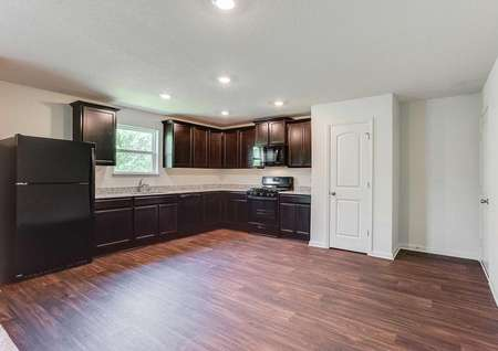 Chippewa kitchen with brown wood flooring, black appliances, and brown cabinets