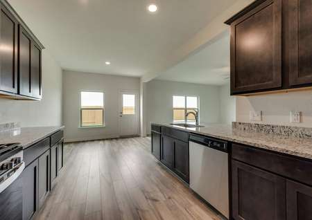 The kitchen is open to the dining room in this plan.