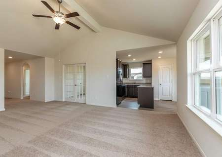 Sabine great room with light brown carpeting, vaulted ceilings, and access to the kitchen and dining area