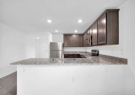The kitchen's granite countertops, upper-wood cabinets and stainless steel appliances.