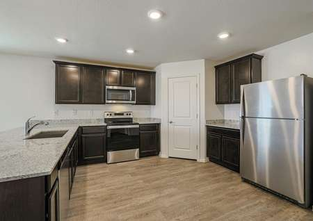 An incredible kitchen with an undermount sink, stainless appliances and sprawling granite countertops.