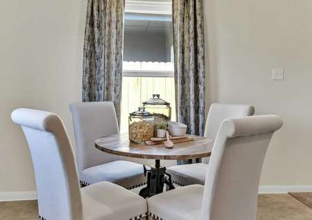 Walnut staged dining area with four white chairs around a small wooden table and tall drapes hanging over the window in the background