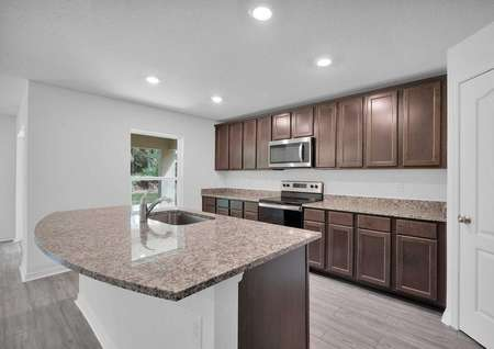 Kitchen angle showcasing tall, upper-wood cabinets and a kitchen island with a sink.