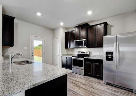 Carson single-family home kitchen with brown cabinets, stainless steel appliances, and large granite island with undermount sink