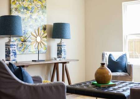 Driftwood staged family room with matching decorative lamps with navy blue shades, artwork hanging on the wall, and grey chair with blue pillow