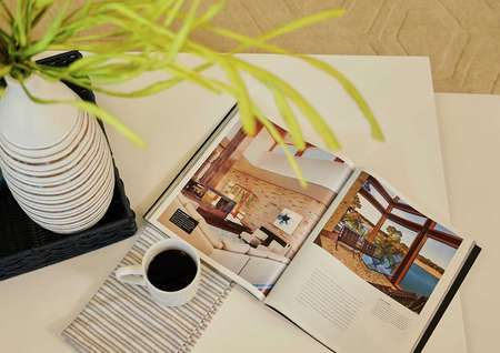 Trace living room with coffee table, cup of coffee, and open book