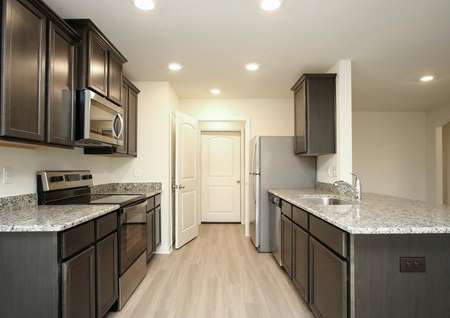 Modern kitchen with dark brown cabinets, gray granite counters, pale plank flooring, recessed lighting and stainless appliances, breakfast overlooks dining room with archway detail.