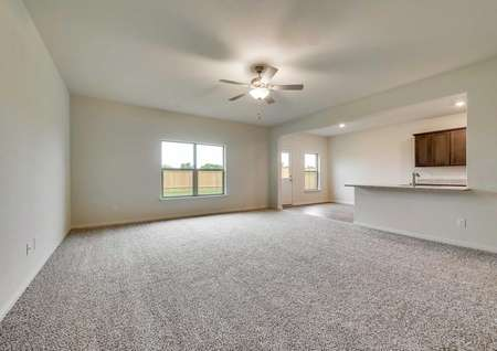 Oakmont model living room with carpet and ceiling fan, view of the open floor plan with kitchen in the background