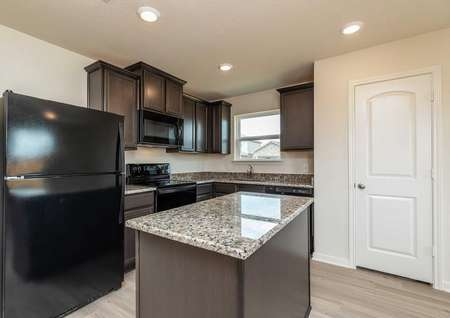 Sabine kitchen with granite countertops, black appliances, and custom brown cabinets