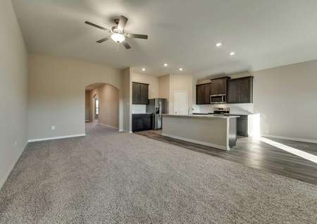 Open layout with large family room and kitchen with brown cabinets and stainless steel appliances.