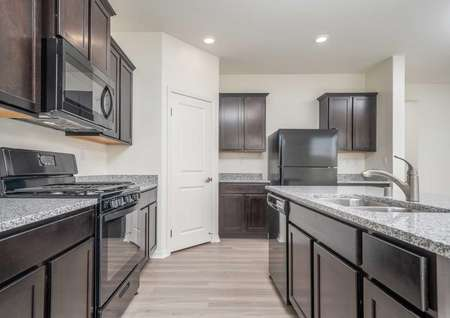 Laguna with brown cabinets, granite countertops, and black appliances