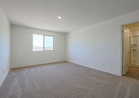 Spacious master bedroom with tan carpet, an amazing window, and an attached master bathroom.
