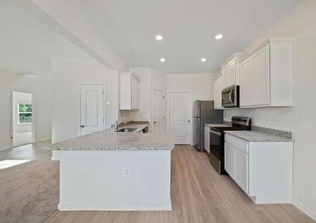 The beautiful kitchen of the Chantilly includes white cabinetry, light gray granite, light plank flooring, stainless appliances, recessed lighting and a long breakfast bar overlooking the family room.