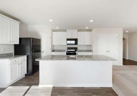Avery kitchen with abundant white cabinets, granite counters, and black appliances