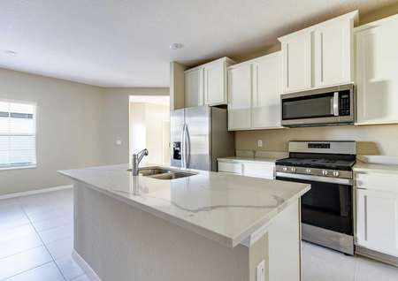 The kitchen with an island, white wooden cabinets, quartz countertops and stainless steel appliances in the Wekiva floor plan.