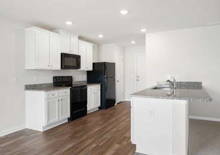 Burke kitchen with grey granite counters, white cabinetry, and wood floors