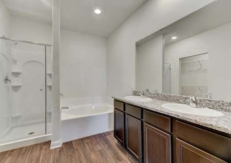 Travis bathroom with two drop-in sinks, granite countertop, and separate shower and bathtub