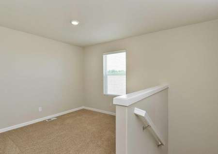 The Northwest Cypress game room is shown with brown carpet and short wall with stair rail.