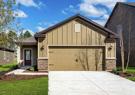 The Alafia floor plans model home that has a two-car garage and a front yard with grass and two small trees.