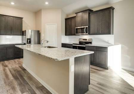 Kitchen with white tile backsplash, brown cabinetry and granite countertops.