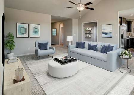 Staged living room with blue couch, vaulted ceiling and access to the kitchen.