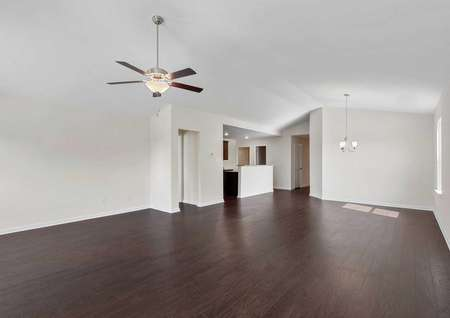 The Claireborne model home living room is equipped with vinyl wood style flooring and ceiling fan, the open room showcases the formal dining room withchandelier, and a glimpse of the kitchen in the left rear