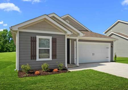 Close up of the Clairborne model home with grey and tan siding, white trim, shutters, shingle roof, and white single car garage