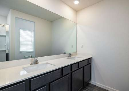 The master bedroom has its own full bathroom, which includes a double-sink vanity.