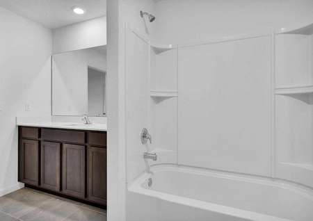 Sunnyside bathroom with white shower/bath combo, brown cabinetry, and recessed light
