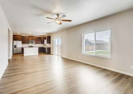 Roosevelt great room with wood floors, light grey walls with white trim, and ceiling fan