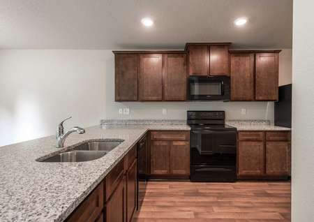Charleston kitchen with granite counters, undermount sink, and brown cabinets